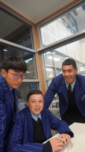 three STC students in blue blazers around a desk