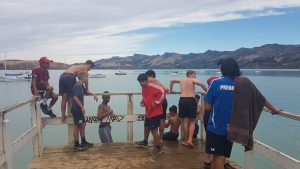 St Thomas of Canterbury College students on a jetty looking at the yachts on the sea