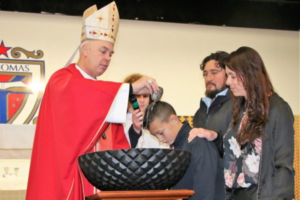 St Thomas of Canterbury College student being baptisedy