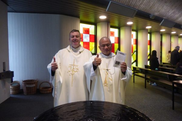 Two catholic priests giving thumbs up