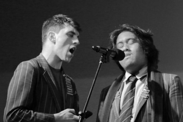 St Thomas of Canterbury College boys on stage singing into microphone