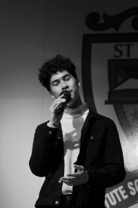 BSt Thomas of Canterbury College boy on stage singing into microphone
